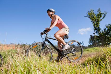 Woman mountain biking on country trackの写真素材 [FYI02124324]