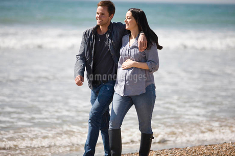 A pregnant woman and her partner walking on the beachの写真素材 [FYI02124335]