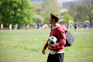 A young man standing in the park, carrying a football and a sports bagの写真素材 [FYI02124336]