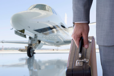 Close Up Of Businessman With Briefcase By Private Airplaneの写真素材 [FYI02124340]