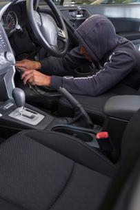 Car thief hotwiring car to stealの写真素材 [FYI02124341]