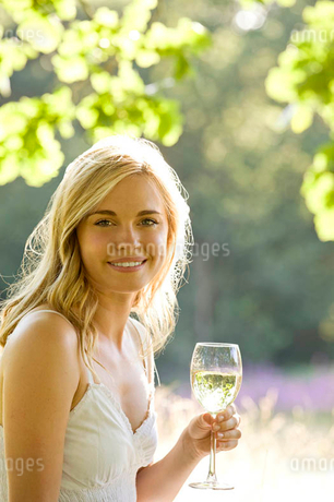 A young woman drinking a glass of white wineの写真素材 [FYI02124347]