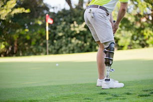 Male Golfer With Artificial Leg On Course Putting Ball On Greenの写真素材 [FYI02124350]
