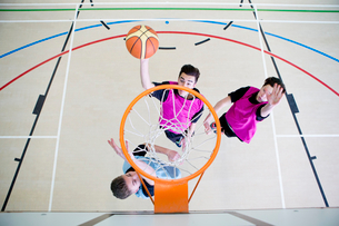 High school students playing basketball in gym classの写真素材 [FYI02124360]
