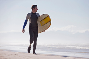Surfer With Artificial Leg Standing On Beachの写真素材 [FYI02124362]