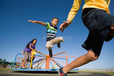 Children jumping off merry-go-round at playgroundの写真素材 [FYI02124378]