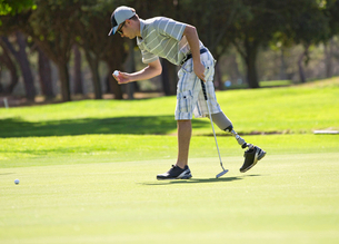 Male Golfer With Artificial Leg On Course Putting Ball On Greenの写真素材 [FYI02124408]