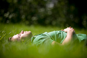 A young man lying on the grass, listening to musicの写真素材 [FYI02124414]