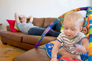 Stressed Mother Watches Baby Son Playing With Toys On Sofaの写真素材 [FYI02124417]