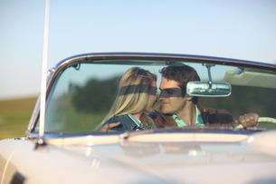 Romantic Couple Driving On Country Road In Open Top Carの写真素材 [FYI02124422]