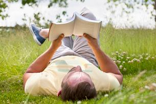 Man reading book relaxing in sunny summer rural grassの写真素材 [FYI02124438]
