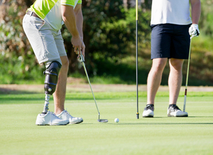 Male Golfer With Artificial Leg On Course Putting Ball On Greenの写真素材 [FYI02124440]