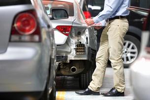 Insurance assessor inspecting damaged vehicleの写真素材 [FYI02124443]