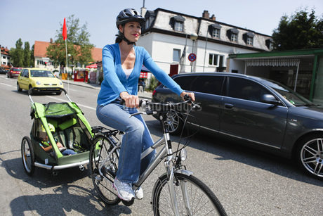 Portrait of mid adult woman riding bicycle with daughter in rearの写真素材 [FYI02124483]
