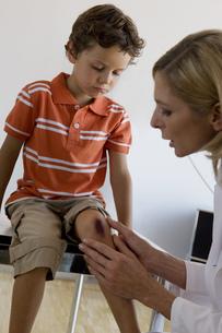 Doctor checking boy's scraped knee in doctor's officeの写真素材 [FYI02124493]