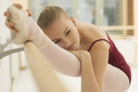 A ballet dancer stretching her leg on the barreの写真素材 [FYI02124500]