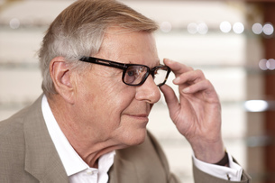 Senior man choosing eyeglasses in optician's officeの写真素材 [FYI02124508]