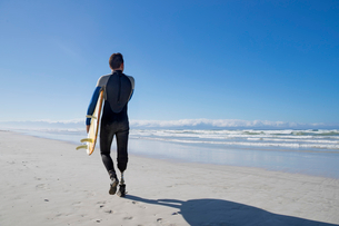 Surfer With Artificial Leg Standing On Beachの写真素材 [FYI02124509]