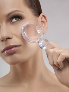 Portrait of young woman holding magnifying glass, studio shotの写真素材 [FYI02124510]
