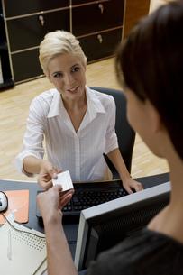 Woman handing receptionist business cardの写真素材 [FYI02124514]