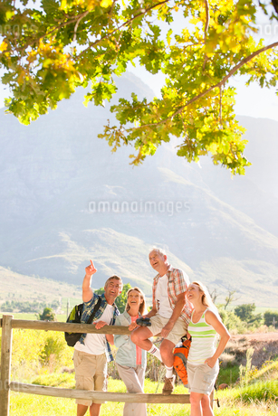 Two generation family out for walk resting on fence in countrysideの写真素材 [FYI02124515]