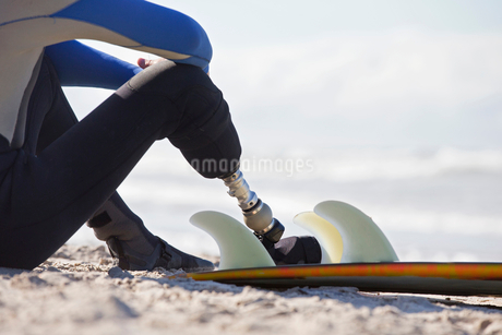 Close Up Of Surfer With Artificial Leg Sitting On Beachの写真素材 [FYI02124522]