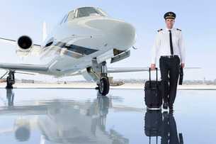 Pilot Of Private Jet Standing By Aircraft In Hangarの写真素材 [FYI02124523]