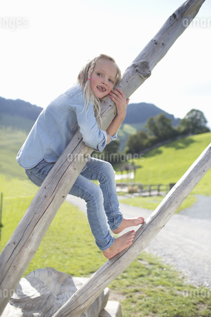 Young Girl Playing On Dead Tree In Countrysideの写真素材 [FYI02124529]