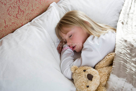Young girl asleep in her bed with a teddy bearの写真素材 [FYI02124541]