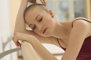 A ballet dancer resting on the barreの写真素材 [FYI02124548]