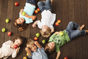 A group of young children laying on wooden decking surrounded by a selection of applesの写真素材 [FYI02124554]