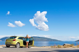 Woman at car looking at sunny ocean viewの写真素材 [FYI02124555]
