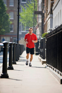 A young man jogging in the street, listening to musicの写真素材 [FYI02124566]