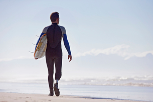 Surfer With Artificial Leg Standing On Beachの写真素材 [FYI02124570]
