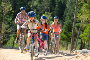 Family riding mountain bikes in forestの写真素材 [FYI02124574]