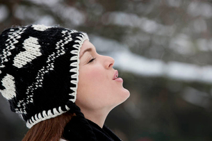 A young woman wearing a woolen hat, breathing into the cold airの写真素材 [FYI02124591]