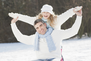 Man and daughter playing in snow, portraitの写真素材 [FYI02124600]
