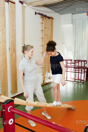 Young schoolgirl balancing on ladder in gym with female gym teacherの写真素材 [FYI02124603]