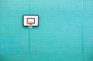 Basketball hoop hanging on turquoise brick wall in gymの写真素材 [FYI02124620]