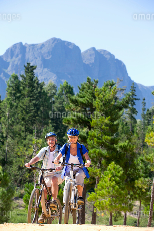 Older couple riding mountain bikes in forestの写真素材 [FYI02124628]
