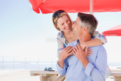 Smiling couple hugging under umbrella at waterfront tableの写真素材 [FYI02124629]