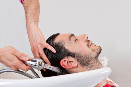 A male hairdresser washing a male clients hair, close upの写真素材 [FYI02124632]