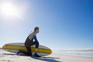 Surfer With Artificial Leg Kneeling On Beachの写真素材 [FYI02124648]