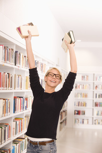 Student holding up textbooks in libraryの写真素材 [FYI02124675]