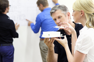 Mature man and young woman constructing architectural modelの写真素材 [FYI02124682]