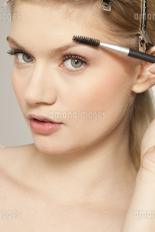 Portrait of young woman applying make upの写真素材 [FYI02124683]