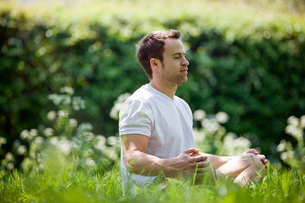 A young man meditating outdoorsの写真素材 [FYI02124694]