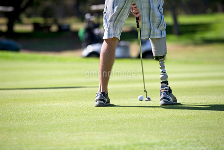Close Up Of Male Golfer With Artificial Leg Putting Ball On Greenの写真素材 [FYI02124710]