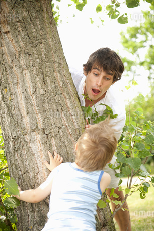 Son surprising father behind tree in parkの写真素材 [FYI02124735]