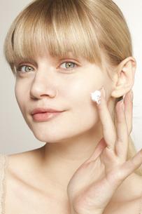 Portrait of young woman applying moisturizerの写真素材 [FYI02124751]